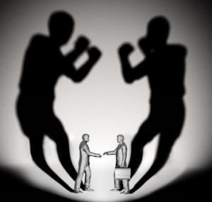 Two businessman casting a shadow shaped like two fighters